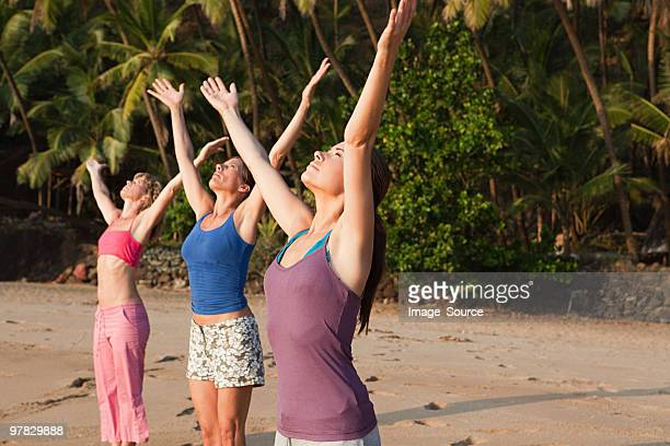 Women practicing yoga on a beach