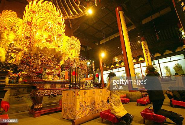 Women pray before a Buddhist statue during New Year's celebrations at Longhua Temple in Shanghai 01 January 2005 For Chinese when the new year comes...