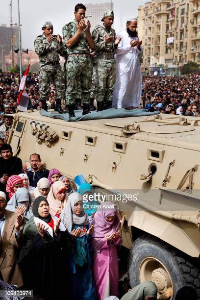 Women pray next to a tank where the top soldiers pray during antigovernment protesters in the Friday prayer during the protests in Tahrir Square...