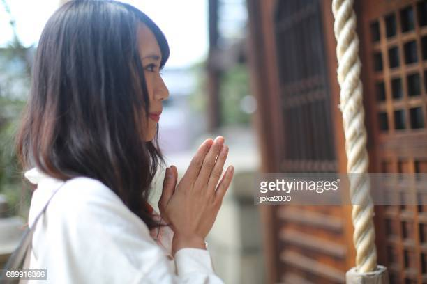 women praying at shrine in kyoto - shrine stock pictures, royalty-free photos & images