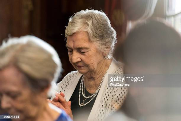women praying in church with eyes closed. focus on background - chapel stock pictures, royalty-free photos & images