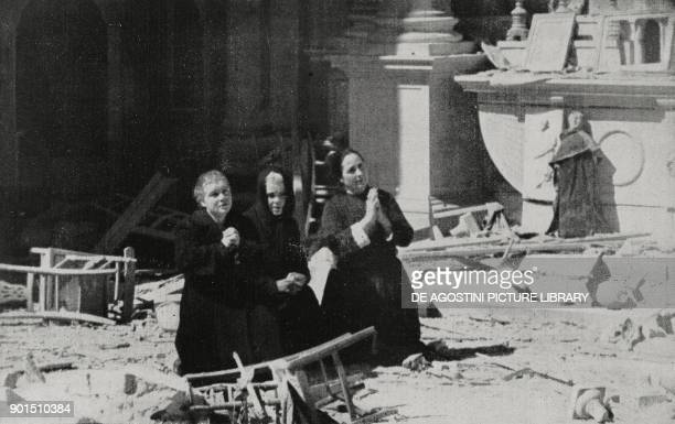 Women praying in the ruins of a church hit by allied bombing Cagliari Italy World War II from L'Illustrazione Italiana Year LXX No 24 June 13 1943