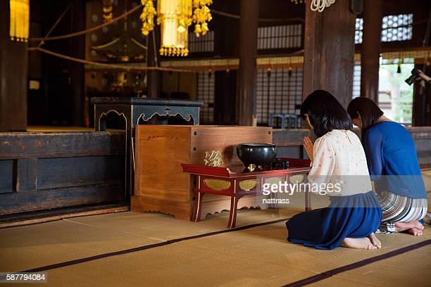 women praying inside a buddhist temple - mulher orando de joelhos imagens e fotografias de stock