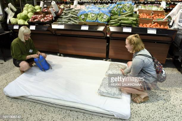 Women prepare a makeshift bed in a local grocery store that invites customers for a sleepover to cool off as the heatwave in Europe continues in...