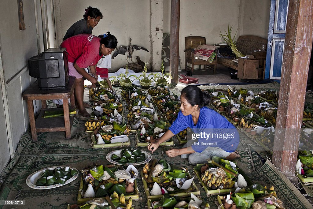 Women prepare foods as an offering during the Cembengan ritual 'Manten Tebu' on April 6, 2013 in Yogyakarta, Indonesia. The Cembengan ritual, performed to bring about a good season's sugarcane crop, is held annually before the milling and processing season starts in Indonesian sugar mills.