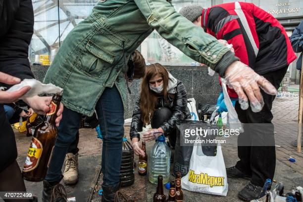 Women prepare Molotov cocktails for antigovernment protesters near Independence Square on February 20 2014 in Kiev Ukraine Dozens of protesters were...