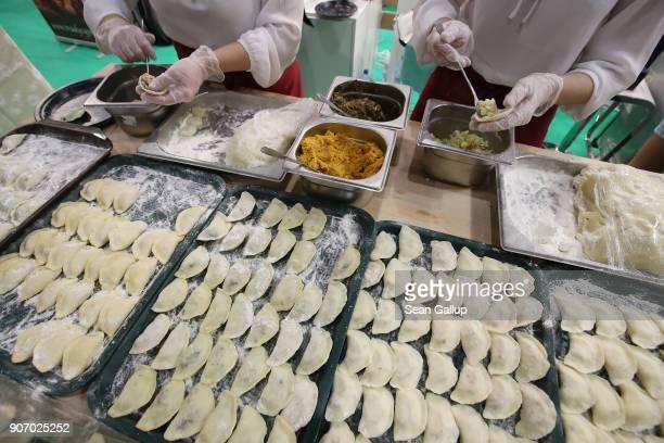 Women prepare Polish dumplings called pierogies at the 2018 International Green Week agricultural trade fair on January 19 2018 in Berlin Germany The...