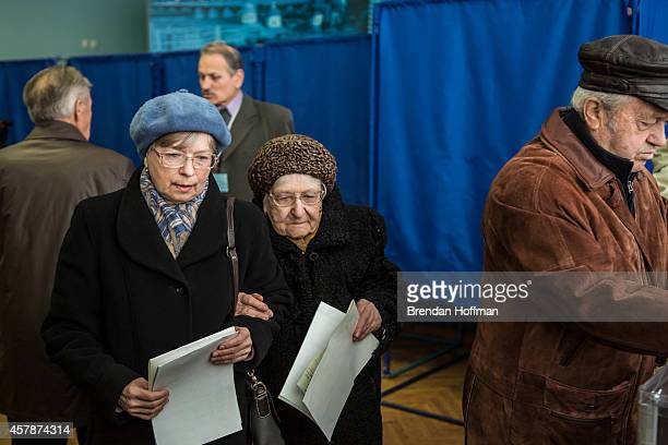 Women prepare to cast their ballots for parliamentary elections at a polling station on October 26 2014 in Kiev Ukraine Although a low turn out is...