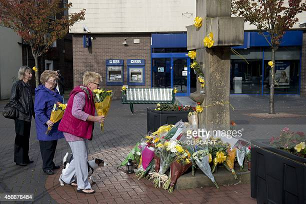 Women prepare to place a floral tribute at the base of the Eccles Cross for murdered aid worker Alan Henning in Eccles north west England on October...