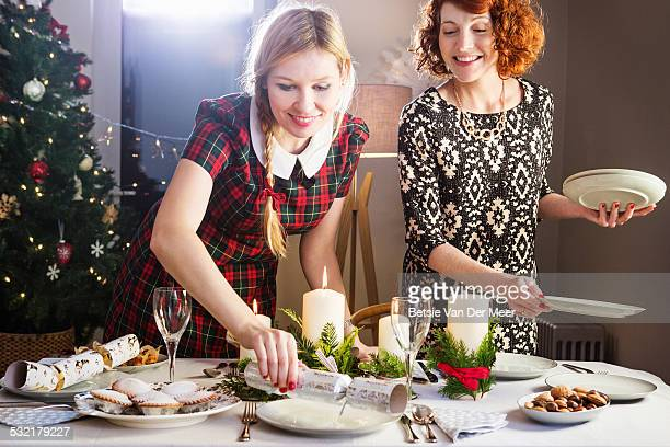 Women preparing Christmas dinner table.