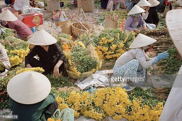 Women preparing flowers for market stall, Vietnam