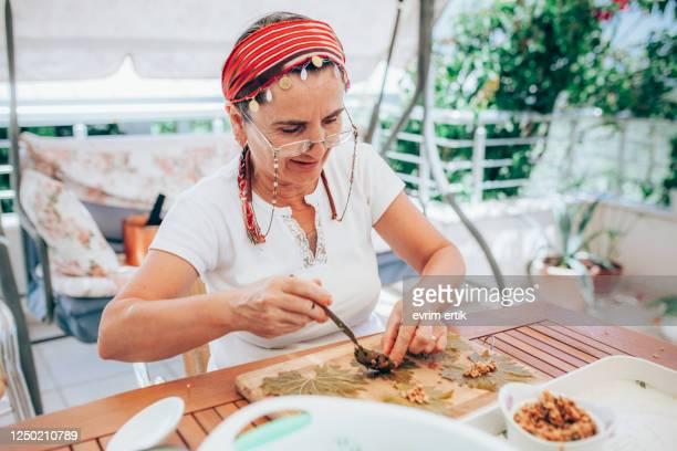 women preparing grape leaves with rice - dolmades stock pictures, royalty-free photos & images