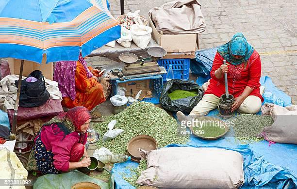 Women preparing spices inside Marrakech souk. Morocco.