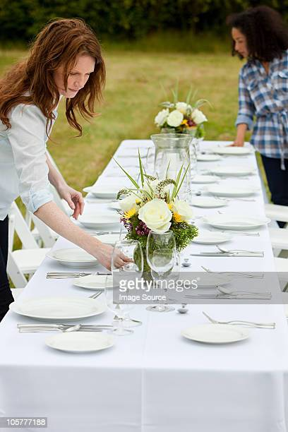 Women preparing table for dinner party in a field