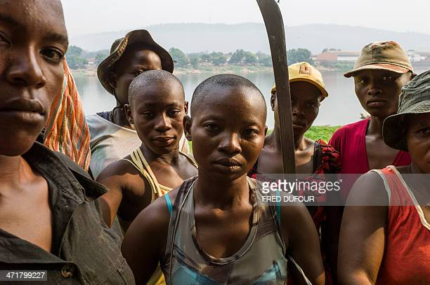 """Women, presenting themselves as anti-balaka and """"Amazons"""" protecting their island from the members of the ex-Seleka, pose with machetes on the Mbongo..."""