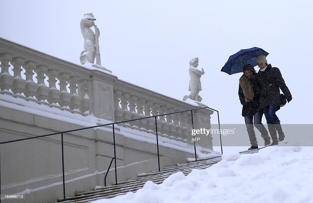 Women protect themselves from snow with an umbrella in the gardens of the Belvedere Palace in Vienna on March 26, 2013.