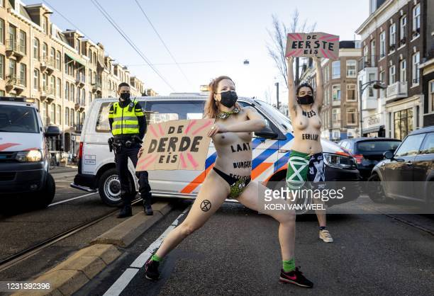 Women protest during a demonstration by Extinction Rebellion outside the Overtoom in Amsterdam-West, as police move some of the 80 activits on, in...