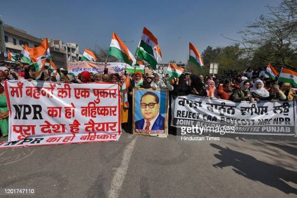 Women protesters hold banners and wave the tricolour ahead of their march to Home Minister Amit Shah's residence, at Shaheen Bagh, on February 16,...