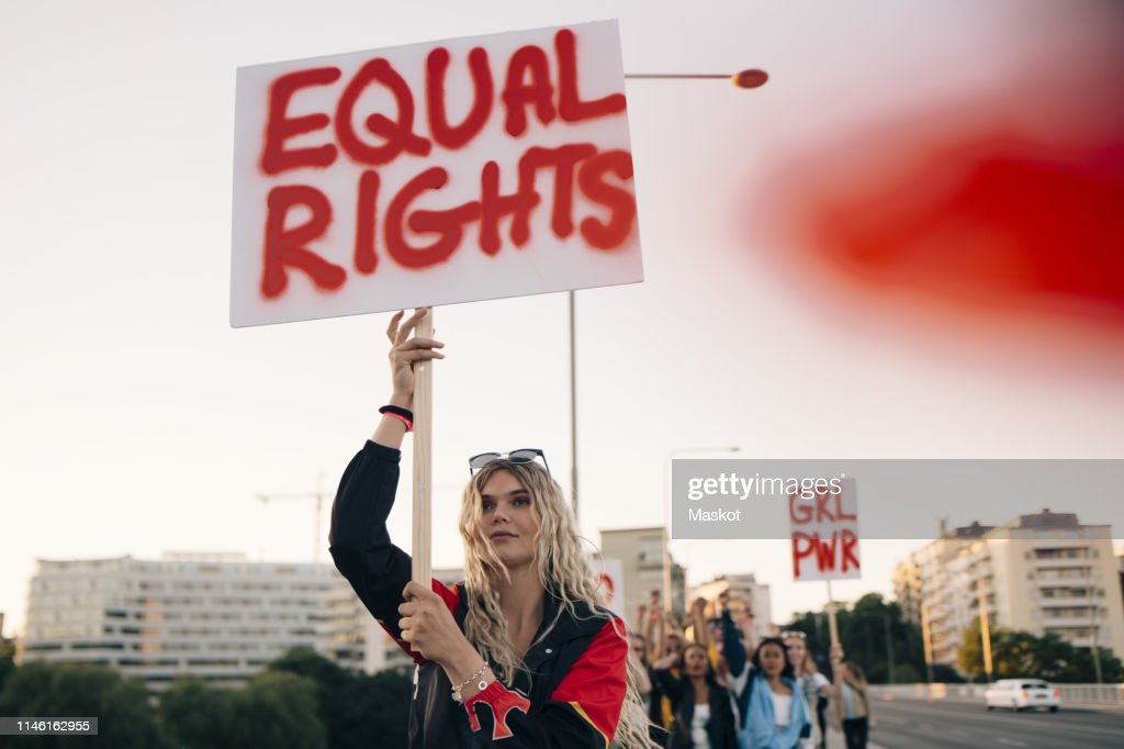 Women protesting with friends for equal rights in city against sky : Stock Photo