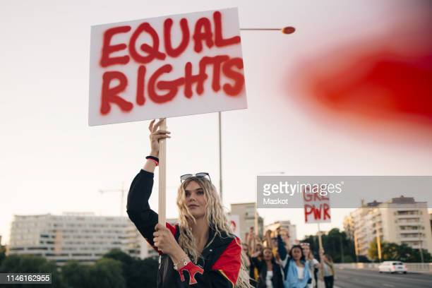 women protesting with friends for equal rights in city against sky - igualdad de genero fotografías e imágenes de stock