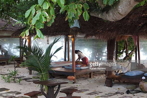 Women provide Thai massage for foreign tourists under huts by the sea on Long Beach on October 19 in Koh Phi Phi Don, Thailand.