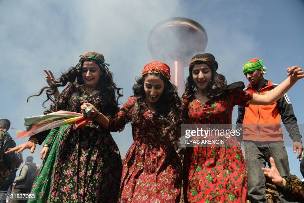 Women psoe in front of a bonfire as Turkish Kurds gather during Newroz celebrations for the new year in Diyarbakir, southeastern Turkey, on March 21,...