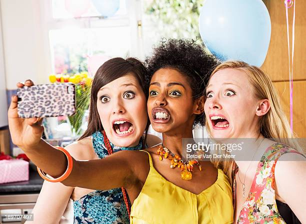 women pulling faces making photos on phone. - pulling funny faces stock pictures, royalty-free photos & images