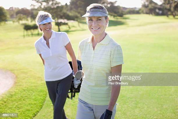 Femmes tirant des voiturettes de golf
