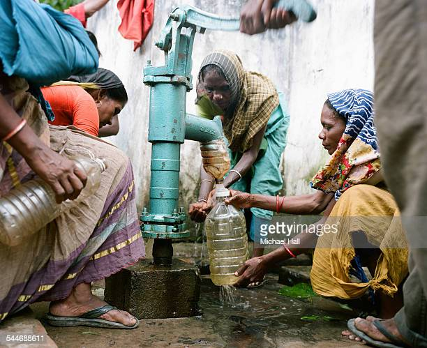Women pumping water from a well
