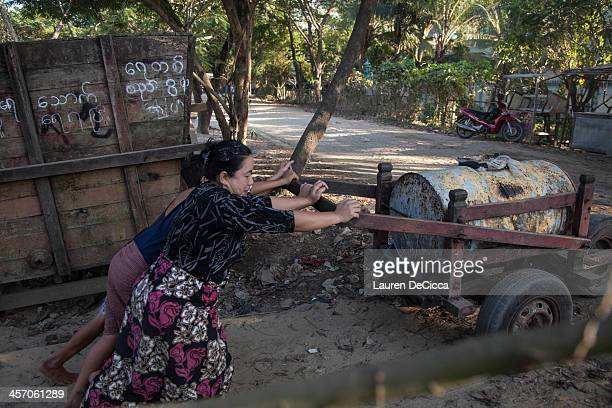 Women push oil drums weighing 240kg on the banks of the Irrawaddy River in the Dala township of Yangon on December 16 2013 in Yangon Myanmar Large...