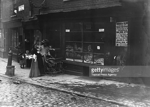 Women pushing a pram past a bakery window in Little Italy a slum area of London in the borough of Holborn