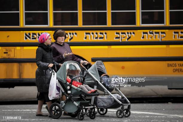 Women pushing strollers walk past the Yeshiva Kehilath Yakov School in the South Williamsburg neighborhood April 9 2019 in the Brooklyn borough of...