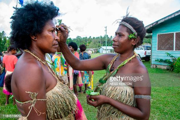 Women put flowers in their hair as people queue to vote at a polling station in the capital Buka in an historical independence vote on November 25...