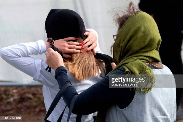 Women put on head scarfs as they arrive at the funeral for two of those killed in the mosque attacks at Memorial Park Cemetery in Christchurch on...