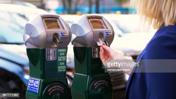 women putting coins into parking meter. - parking meter stock photos and pictures