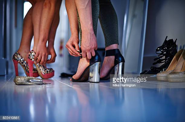 women putting on high heels ahead of night out. - hoge hakken stockfoto's en -beelden