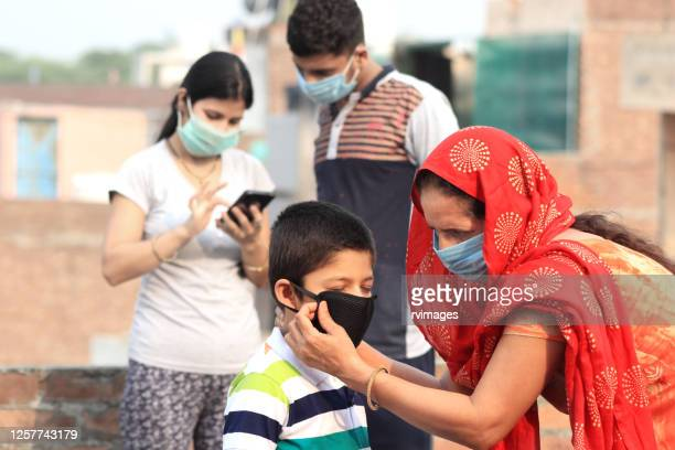 women putting on medical mask to her grandchild - alertness stock pictures, royalty-free photos & images