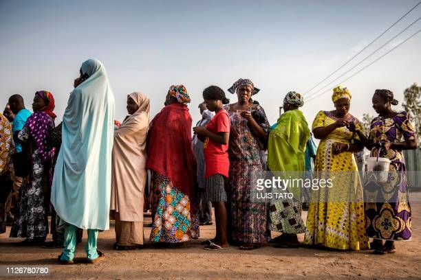 TOPSHOT Women queue to vote early in the morning at Shagari Health Unit polling station a few hours before polls opening in Yola Adamawa State...