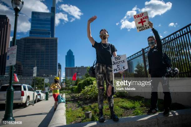 """Women raise signs """"NO JUSTICE NO PEACE"""" and """"FIRST AID"""" to provide food and water to protesters during a march through Center City on June 1, 2020 in..."""
