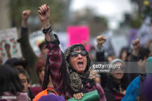 Women raise their fists during the International Women's Day March and Rally on March 5 2017 in Los Angeles California The rally is a lead up to the...