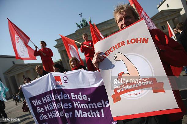 Women rally for equal pay for women compared to men on Equal Pay Day in front of the Brandenburg Gate on March 20, 2015 in Berlin, Germany. Income...