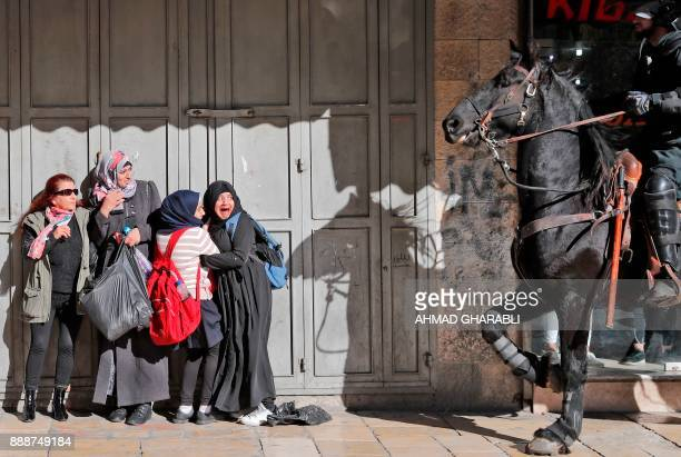 Women react as an Israeli mounted policeman disperses Palestinian protesters on December 9 in East Jerusalem Retaliatory Israeli air strikes on the...