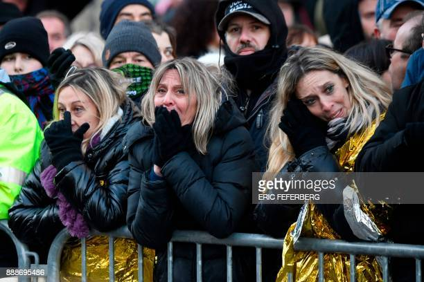 Women react as people gather near to La Madeleine church in Paris on December 9 for the procession of the funeral ceremony for beloved rock star...