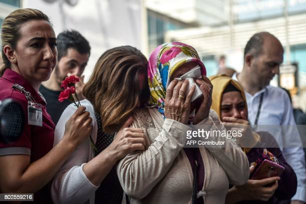 Women react as relatives of victims attend a memorial ceremony on June 28, 2017 at Ataturk International airport in Istanbul, one year since the...