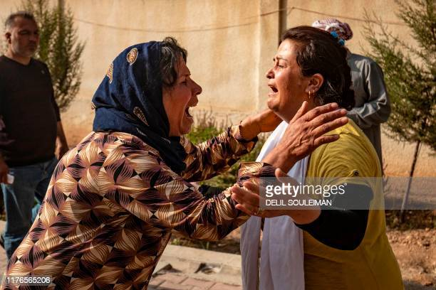 TOPSHOT Women react as the body of a man killed during Turkish shelling in the area surrounding the Syrian Kurdish town of Ras alAin arrives at a...