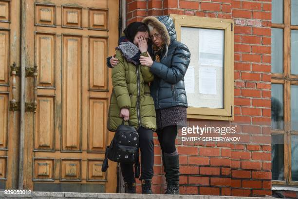 Women react during a funeral service for a victim of a shopping mall fire in the industrial city of Kemerovo in western Siberia on March 28 2018...