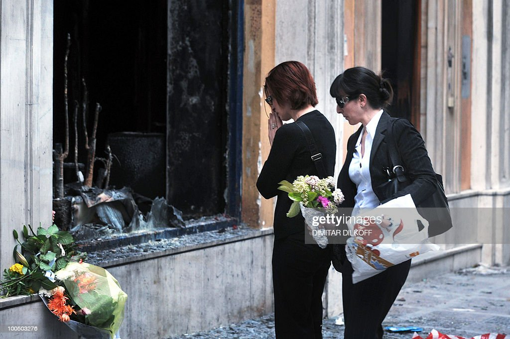 Women reacts as they put flowers in front the branch of the Marfin bank where three people were killed a day earlier in Athens May 6, 2010. A fire-bomb attack on a bank in Greece killed at least three people on May 5, as police fought pitched battles with striking protestors furious at brutal budget cuts designed to avert national bankruptcy.