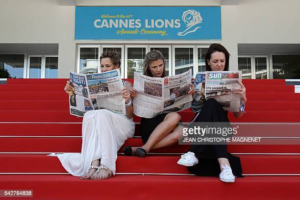 Women read newspapers outside the international advertising festival Cannes Lions 2016 on June 24 2016 in Cannes southeastern France / AFP / JEAN...