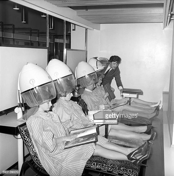 Women reading magazines at the John London Hair and Beauty Saloon whilst under the driers 1960