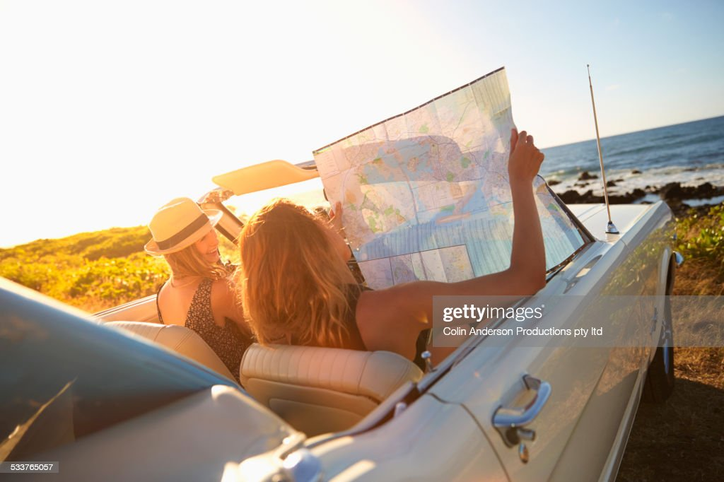 Women reading map in convertible on beach : ストックフォト